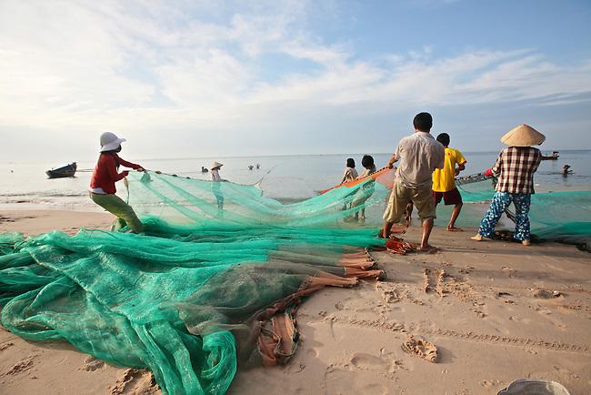 Fishermen haul in a net on the beach in Mui Ne, Vietnam. Nov. 20, 2011.