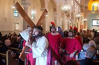 Jesus (portrayed by PJ McNerney) carries the cross during St. Monica Catholic Church's Good Friday Living Stations of the Cross services on Friday, March 29, 2013.