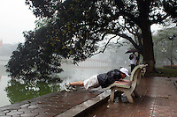 A man uses a park bench to exercise beside Hoan Kiem Lake, Hanoi, Vietnam.. For a county not know for it's sporting prowess, Hanoi, Vietnam's capital, appears to be gripped in a fitness frenzy. Before 6am street corners, parks and lake sides are a hive of activity as keep fit classes, Tai chi and personal exercise regimes are seen in abundance around the city. Particularly noticeable are Women's keep fit classes, often accompanied by loud poor quality western disco beat music as the occupants of the city get fit come rain or shine. Hanoi, Vietnam. 17th March 2012. Photo Tim Clayton