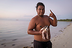 "A local Carolinian man gives the ""shaka"" after bathing his puppy in the lagoon on Saipan's west side. Originally from the Caroline Islands in Micronesia, they are a minority on Saipan who settled there after typhoons damaged their island and before that, around 1815, when many Carolinians settled on Saipan during a period when the native Chamorros were imprisoned on Guam by the Spanish. Their language is one of the official languages along with Chamorro and English."