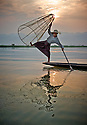 Boy throw his traditional Inle net in the lake in the hope of catching some fish. The shallow waters trap fishes in the conical net.