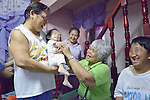 Iluminada Castillo holds her 3-year old grandson Ceyrus in his home in the Malate neighbohood of Manila, while Maria Hilvano exerises the boy's arms. The women are members of Kaisahan ng Magulang at Anak na Maykapansanan (Kaisaka), a mothers' group that carries out community based rehabilitation with families which have members with disabilities.
