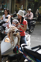 Hanoi<br /> , Vietnam - 2007 File Photo -<br /> <br /> <br /> A young Vietnamese woman wearing western clothes  sit on a scooter while holding a baby, in hanoi street<br /> <br /> <br /> photo : James Wong-  Images Distribution