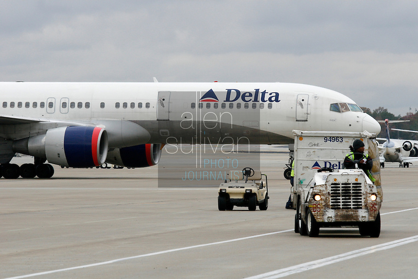 Delta Air Lines planes and workers on the tarmac at Hartsfield-Jackson Atlanta International Airport. US Airways has made a bid to take over Delta Air Lines, which is headquartered in Atlanta.<br />