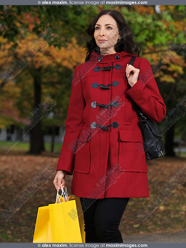 Smiling young beautiful woman walking on a sidewalk wearing a red coat and holding shopping bags