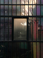 Plant History Glasshouse (formerly the Australian Glasshouse), 1830s, Charles Rohault de Fleury, Jardin des Plantes, Museum National d'Histoire Naturelle, Paris, France. Detail of window panes reflecting the late afternoon light and the twin New Caledonia glasshouse. Through a rectangular window the inside vegetation may be seen beneath the glass and metal structure lit by the afternoon light.