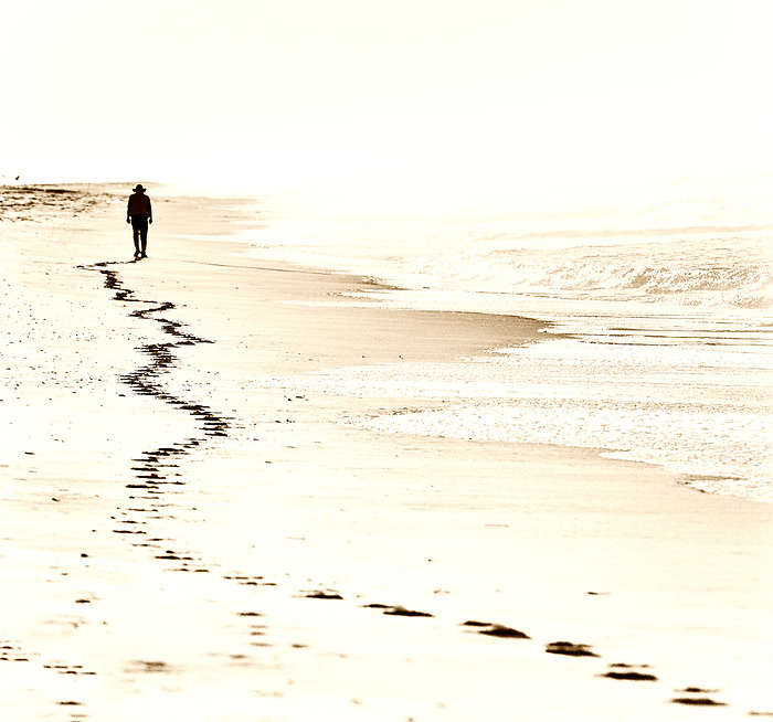 Man and his footsteps on Robert Moses Beach, Long Island, New York
