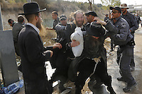 An Ultra-Orthodox Jewish man is pushed away by an Israeli policeman in Ramat Beit Shemesh West of Jerusalem on August 12 2013, after dozens of Haredim protest against desecration of ancient graves were discovered at a new housing construction site. Some 14 Ultra-orthodox Jews were arrested. Photo by Oren Nahshon