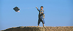 In the Shamshatoo refugee camp, an Afghan boy enjoys flying a kite, a pleasure prohibited by the Taliban..