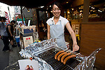 A staffer sees to German sausages cooking on a griddle at Konig, a popular sausage and beer shop near Inokashira Park in the trendy neighborhood of Kichijoji in Musashino City, Tokyo, Japan on 16 Sept. 2012.  Photographer: Robert Gilhooly