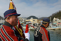 """Fire chiefs on the dock after the event. Housui Gassen (fire-hose battle), Bizen city, Okayama pref, Japan, February 2, 2014. The annual Bizen """"Housui Gassen"""" (fire-hose battle) takes place in the Hinase port area. Opposing teams of fire-fighters spray each other with hoses before the event culminates with a display of coloured water from the hoses."""