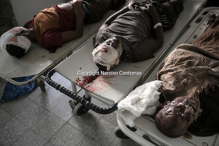 July 05, 2015 - Hajjah, Yemen: The bodies of three civilian lay at the morgue of  Jamhoony hospital in Hajjah city after they arrived from Harad, a border town where a fighter jet of the Saudi-led coalition dropped a bomb over a market place killing 30 and leaving 67 severely wounded. (Photo/Narciso Contreras)