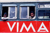 Indian men look out of the windows on a bus with advertising for the 'VIMA Show room'. Hyderabad, India.