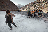A Wakhi man tries to get the yak to come on the frozen Wakhan river..Trekking up to the Little Pamir with yak caravan over the frozen Wakhan river.