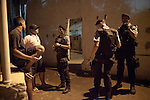 Police Pacification Unit (UPP) officer XXX Pinheiro, left, and her patrol group, check ID's in Complexo do Caju, a complex of a newly pacified favelas in the North Zone, Rio de Janeiro, Brazil, on Saturday, April 27, 2013. <br /> <br /> In the early hours of Sunday, March 3, 2013, about 1,400 Brazilian security forces occupied 13 communities during a joint public security operation to install a Pacifying Police Unit (UPP) in two Rio de Janeiro favelas, Complexo do Caju and Barreira do Vasco. Elite police units backed by armored military vehicles and helicopters invaded the neighborhood in an on-going policing program aimed to drive violent and heavily armed drug gangs out of Rio's poor communities, where the traffickers have ruled for decades. For the community of Caju, that is ADA (Amigos de Amigos).