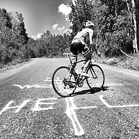 A lone cyclist struggles to climb the steep pitches of the Empire Pass climb, outside of Park City, Utah.