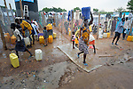 Women and children fetch water in a camp for internally displaced families located inside a United Nations base in Juba, South Sudan. The camp holds Nuer families who took refuge there in December 2013 after a political dispute within the country's ruling party quickly fractured the young nation along ethnic and tribal lines. The ACT Alliance is providing a variety of services, including fresh water, to the more than 20,000 people living in the camp.