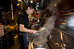 Store manager Yusuke Osako prepares noodles in the kitchen at Hakata Ippudo Ramen's main store in the Daimyo district of Fukuoka City, Fukuoka Prefecture Japan on 08 March 2013.  Photographer: Robert Gilhooly