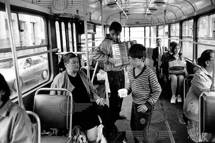©Clive Shirley/Panos Pictures..Poland. Gypsy children playing the accordion on the tram in Warsaw.