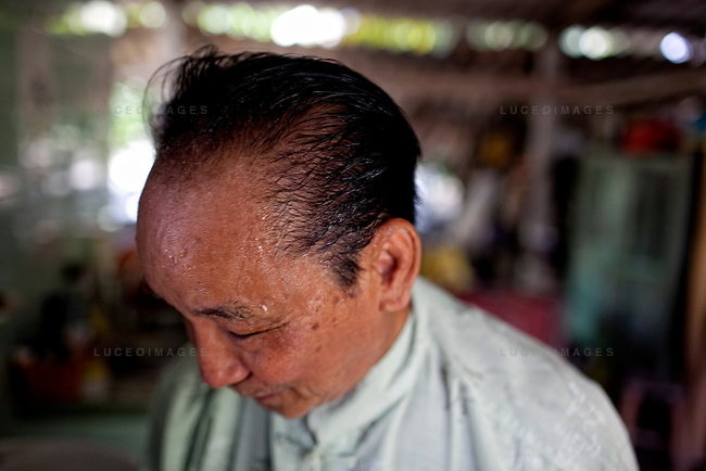 Tran Van Bang, 81, combs his hair with clean water provided by the Tien Phat enterprise in the Luong Hoa Lac commune.