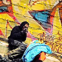 A Colombian drug addict smokes 'basuco' (raw cocaine paste) in front the wall, covered in graffiti artwork in the center of Bogotá, Colombia, 15 February, 2016. A social environment full of violence and inequality (making the street art an authentic form of expression), with a surprisingly liberal approach to the street art from Bogotá authorities, have given a rise to one of the most exciting and unique urban art scenes in the world. While it's technically not illegal to scrawl on Bogotá's walls, artists may take their time and paint in broad daylight, covering the walls of Bogotá not only in territory tags and primitive scrawls but in large, elaborate artworks with strong artistic style and concept. Bogotá has become an open-air gallery of contemporary street art.