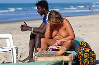 Gambia. Kombo beach. Atlantic ocean. Kombo beach is 25 km away from the capital Banjul. Sex tourism. A white fat topless woman enjoys her reading while her black boyfriend sits near her.  © 2000 Didier Ruef