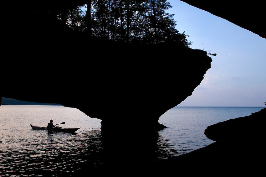 A sea kayaker silhouetted while exploring a cave arch at Trout Point on Grand Island National Recreation Area in Munising Michigan.