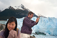 Kathleen Kao shivers from teh cold as she and traveling friend Huw (cq) Whyment, of Swansea, Wales, snaps a photo of teh Perito Moreno glacier in Argentina's Parque Nacional Los Glaciares, Tuesday, Nov. 21, 2006.<br /> <br /> Kao (American) best reached by e-mail at kskao@yahoo.com or 512-791-3992<br /> Whyment best reached by e-mail. He's traveleing for the year. bigholiday@googlemail.com (not gmail)<br /> <br /> (Kevin Moloney for the New York Times)