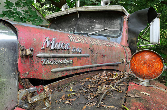 Old and abandoned Mack B truck under a maple tree with dried leaves and twigs across the fender, a B-62 XS model with Thermodyne engine.