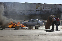 Palestinian protester take shelter during clashes with Israel Defense Forces after the funeral held for three Palestinians killed during IDF operation at Kalandia refugee camp on August 26, 2013 in Ramallah, West Bank. Photo by Oren Nahshon