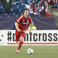 Toronto FC defender Steven Caldwell (13) brings the ball forward.  In a Major League Soccer (MLS) match, the New England Revolution (blue) defeated Toronto FC (red), 2-0, at Gillette Stadium on May 25, 2013.