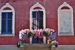 Shuddered windows and a balcony covered with flowers in Morcote, a town on Lake Lugano, Switzerland.