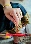 Fine silk thread is produced by a woman spinning silk the traditional Lao way for weaving at Carol Cassidy Lao Textiles, Vientiane, Laos.