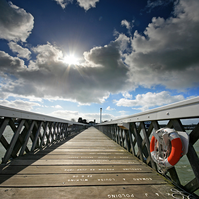 The wide-angle lens and low point-of-view helps to create a dramatic vanishing point looking back towards the town from Yarmouth Pier on the Isle of Wight.<br /> <br /> Two shot vertical panorama created from two frames using the Sigma 10-20mm at f10 1/250<br /> <br /> Part of the Ocean Seen - Oceanic Photography Exhibition.<br /> <br /> Sponsored by Wightlink - Dimbola Museum &amp; Galleries, Freshwater Bay, Isle of Wight - 29th June to 2nd September 2012.<br /> <br /> A collaborative summer show, bringing together three great oceanic photographers to celebrate the way we interact with our great British coastline.