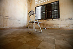 A metal folding chair sits inside a mass detention cell at Tuol Sleng prison in Phnom Penh, Cambodia. The numbers on the wall mark where prisoners lay when shackled together by means of a large iron bar. Prisoners slept with their heads in opposite directions, and were not issued mats, mosquito nets or blankets. They were also prohibited from speaking to each other. Prisoners were kept under these conditions except for daily inspections and interrogation sessions. All but a handful of the estimated 17,000 people who passed through Tuol Sleng were eventually transferred to the Killing Fields and murdered. March 1, 2012.