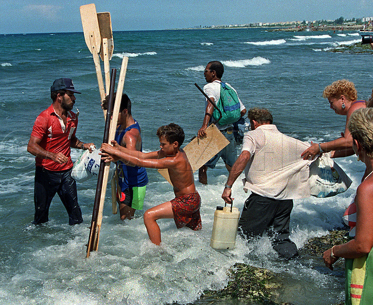 8/1994-Al Diaz/Miami Herald--In 1994 Cuban balseros turned the tiny fishing village of Cojimar into a major point of embarkation for thousands seeking a better life. Here, Cubans walk into the ocean as they prepare to carry their pocessions onto a raft bound for the U.S...
