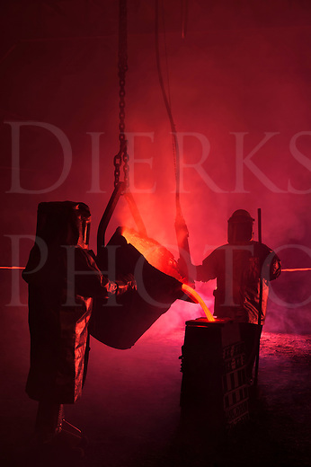 Pouring molten iron in a steel mill reenactment, steelworkers using with ladle bucket...hot, smoky, and dangerous in the steel mill at Bethlehem, Pennsylvania, USA.