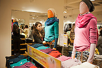 An employees adjusts merchandise at the grand opening of the Uniqlo Flagship store on Fifth Avenue in New York on Friday, October 14, 2011.  The store is a staggering 89,000 square feet on multiple levels and is Fast Retailing's second store in the United States with a third opening next week in the Herald Square shopping district. The largest store on Fifth Avenue filled to the brim with affordable clothing it competes with stalwarts such as the Gap and Zara which are in the immediate proximity. Fast Retailing plans on opening 200 to 300 stores worldwide until 2020 and currently has 1000 stores. (© Richard B. Levine)