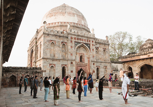 Young men and women practicing early morning yoga at the Bara-Gumbad Tomb. The Bara-Gumbad Tomb is one of two square-plan tombs in Lodi Gardens, New Delhi, India. It was built during the Lodi Period (1451 - 1526). Adjoining the Bara-Gumbad is a mosque, and in front of the mosque is a mihman-khana, or guest house for pilgrims.