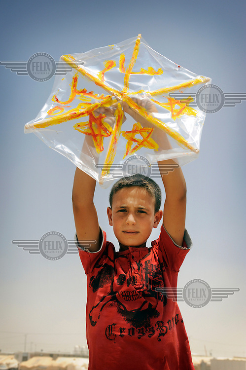 Syrian refugee Basil holds up a kite which he has made. On the kite is a personal message of peace for his country. Basil has been a refugee in Za'atari camp for four months now. He fled the violence in Syria with his mother, three brothers and three sisters, but his father is still there. Basil's definition of freedom is feeling safe. 'We used to feel that before the violence started' he said. 'The thing I want most is to hug my father when I go back to Syria. Basil wrote 'Peace' on his kite. /Felix Features