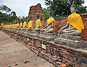TH00256-00...THAILAND  - A row of Buddhas with surround the main chedi at Wat Chai Mongko in Ayutthaya.