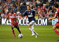 Chivas forward Justin Braun (17) dribbles between Chicago forward Partrick Nyarko (14, left) and midfielder Baggio Husidic (9, right).  The Chicago Fire tied Chivas USA 1-1 at Toyota Park in Bridgeview, IL on May 1, 2010.