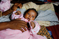 Kroo Bay, Freetown, Sierra Leone...Story on child and maternal health in the Kroo Bay slum community in Freetown, Sierra Leone, which has the World's worst infant and maternal mortalitly rates. One in 4 children die before they reach the age of 5 and one in 6 mothers dies during child birth (in the UK, the rate is one in 3,800)...The Kroo Bay Community Health Centre has a catchment area of over 8,000 people but lacks adequate facilites to provide even basic care. The clinic lacks even the basics, such as bedpans, surgical spirits and cotton wool. It has no electricity and clean drinking water must be fetched from the nearby well everyday...Maseray Kamara at home with her newborn baby Fatmata, who is nine weeks old. Maseray is suffering from blocked glands in her breast, which is severely swollen and painful and is restricting her ability to breastfeed her child. However, she is unable to afford the fees to have her condition treated at hospital....© 2007 Aubrey Wade. All rights reserved.