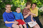 Mother sitting on wall in garden with three sons with autism.  MR