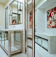 A corner of the bathroom where stainless steel, marble and mirrored-glass are combined in an atmosphere of 30s glamour