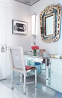 A mirrored dressing table with a matching chair is tucked into a corner of the dressing room which has a mirrored mosaic floor