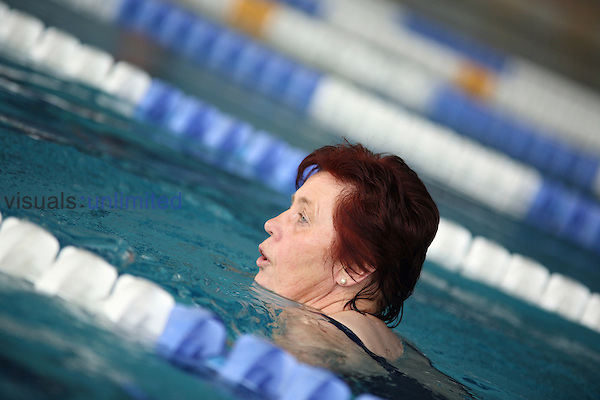 older woman doing her lane swimming in the indoor swimming pool