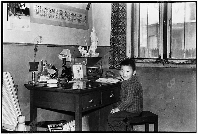 Li's son, Xiaohan, in the family home in Harbin sitting at the desk under which Li cut a hole in 1968 to hide his negatives. 19 February 1973.
