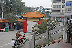 a man wheels a motorbike through the courtyard, and toward the pagoda gate, of a Buddhist temple in Guilin, China