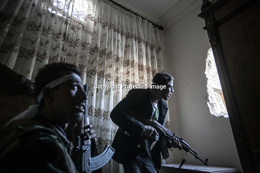 In this Thursday, Nov. 01, 2012 photo, rebel fighters watch over their enemy's position as they await for the army troops to enter into one street during clashes in the nearby Karmal Jabl battlefield in Aleppo, the Syrian's largest city. (AP Photo/Narciso Contreras).